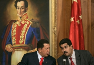The late President Hugo Chávez and the now Acting President Nicolás Maduro confer under a portrait of Latin American hero Simón Bolivar. (AP/File)