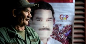 Miguel Guevara, 73, a Chávez loyalist, stands in his home in Caracas next to an election poster for Chávez's chosen succesor, Nicolás Maduro. (Leo Ramirez/AFP/Getty Images)