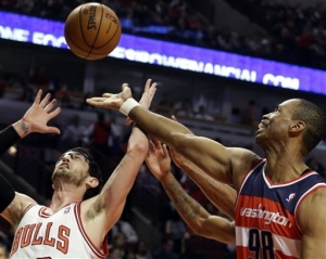 In this April 17, 2013 file photo, Washington Wizards center Jason Collins, right, battles for a rebound against Chicago Bulls guard Kirk Hinrich. Collins is the first male professional athlete in the major four American sports leagues to come out as gay.