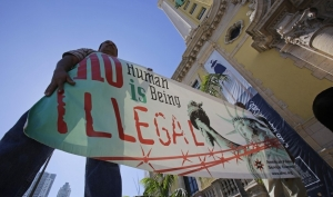 Immigration reform activists hold a sign in front of Freedom Tower in downtown Miami, Monday, Jan. 28, 2013.